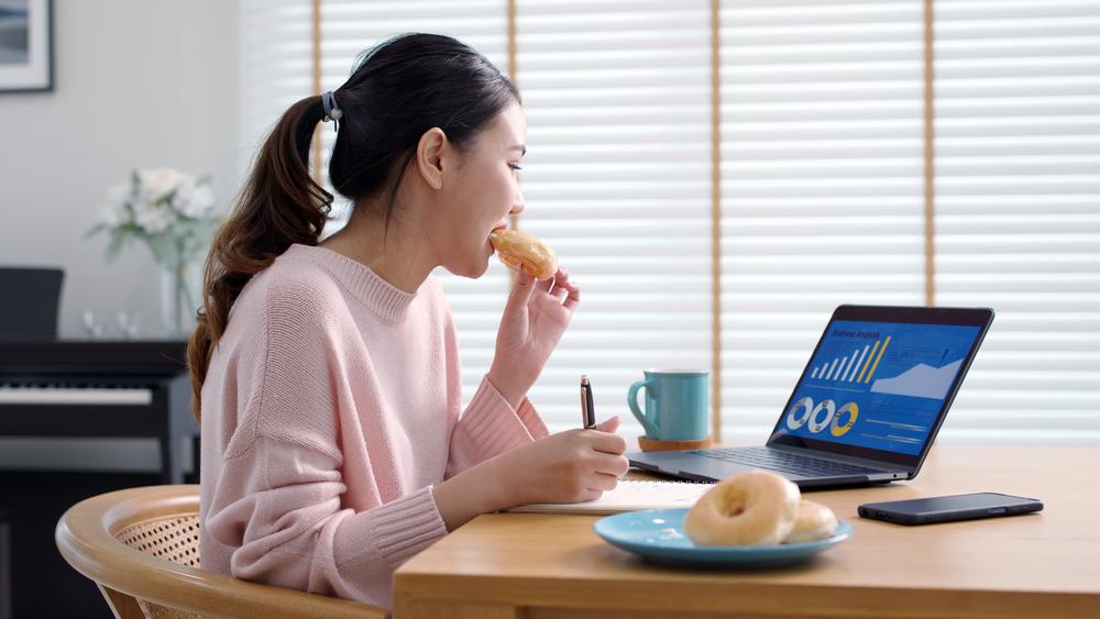 リモートワーク中についつい甘いドーナッツを食べてしまう女性